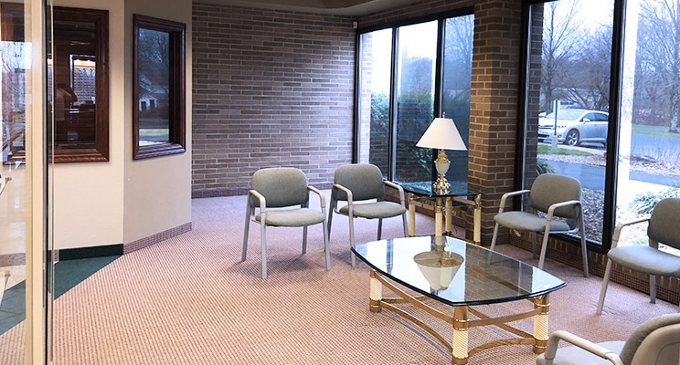 waiting area in Eyecare Center with glass tables and brick walls
