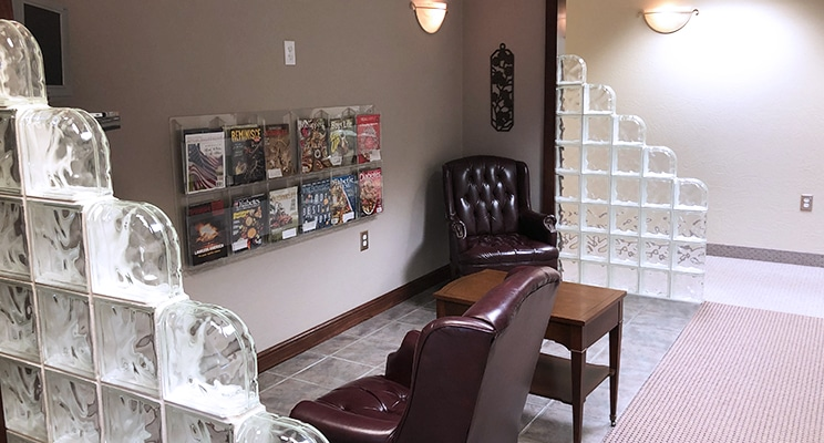 waiting area with wingback chairs and magazine rack on wall